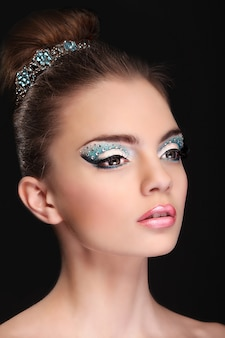 Portrait of beautiful young girl with fashion make-up isolated on black