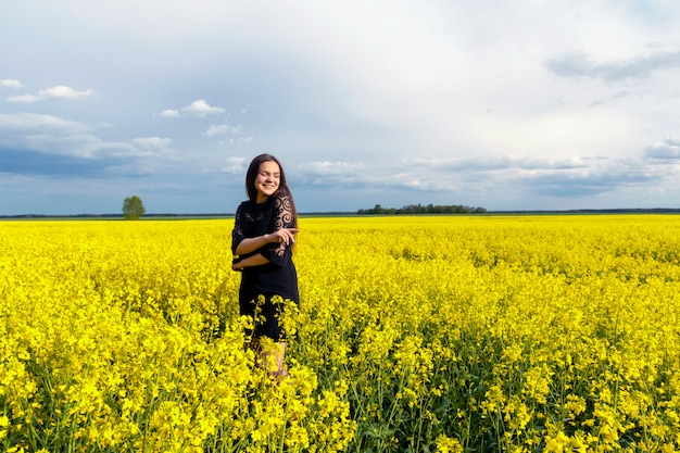 Portrait of a beautiful young girl with long hair in black dress is standing in yellow field.