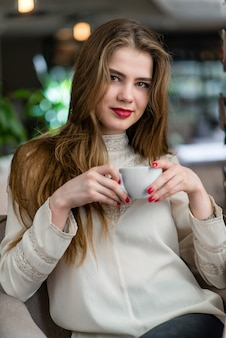 Portrait of beautiful young girl with professional makeup and hairstyle in restaurant.