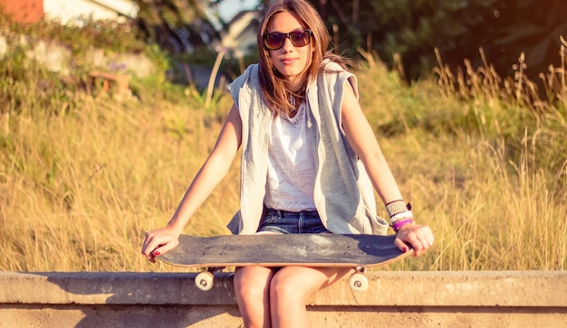 Portrait of beautiful young girl with short shorts and skateboard sitting over the wall on a summer day. warm tones edition.