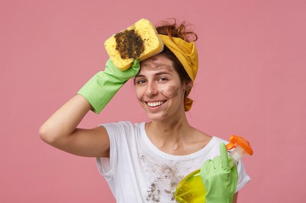 Ritratto di bella giovane casalinga con i vestiti sporchi e la faccia che tiene la scopa e lo spruzzo di lavaggio che tiene la mano sulla testa che sembra stanca ma felice di finire il lavoro. donna carina stanca che fa la pulizia della casa