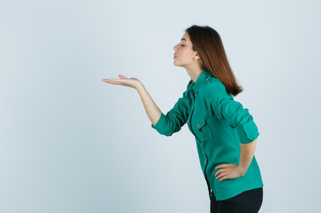 Ritratto di bella giovane signora che soffia aria bacio con le labbra imbronciate in camicia verde e che sembra pacifica