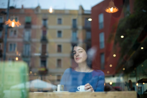 Portrait of beautiful young lady drinking coffee and looking at camera through glass while sitting at table in a cafe