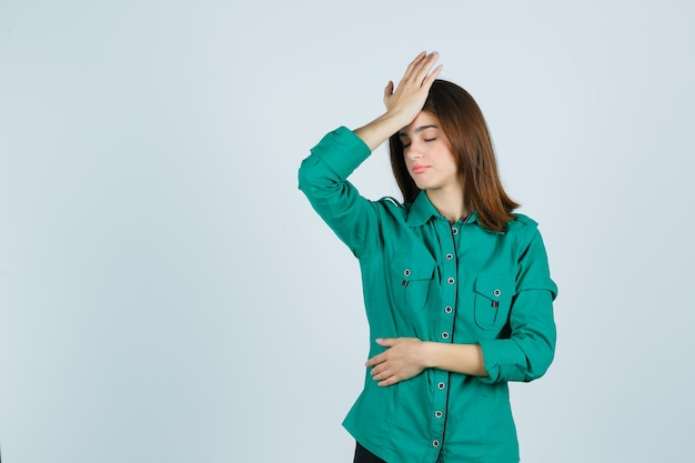 Portrait of beautiful young lady feeling headache in green shirt and looking tired front view