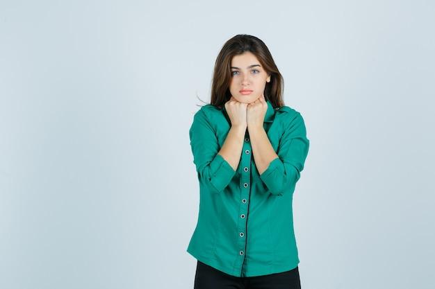 Ritratto di bella giovane signora che tiene i pugni sotto il mento in camicia verde e che sembra vista frontale spaventata