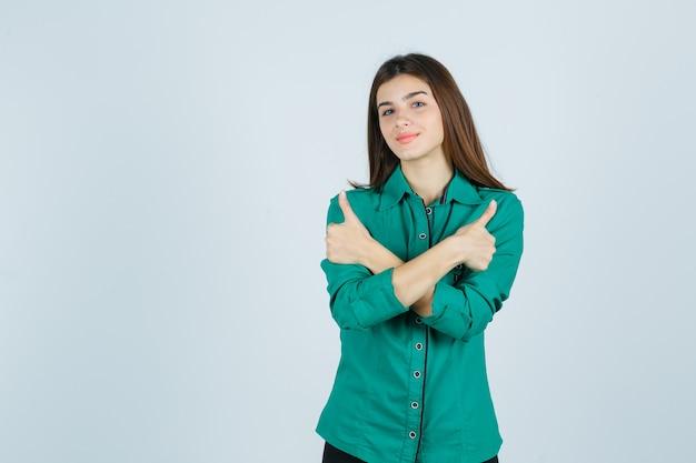 Ritratto di bella giovane signora che mostra i doppi pollici in su in camicia verde e che sembra vista frontale allegra