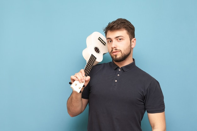 Portrait of a beautiful young man with a beard and a dark t-shirt, standing on blue with a ukulele in his hands