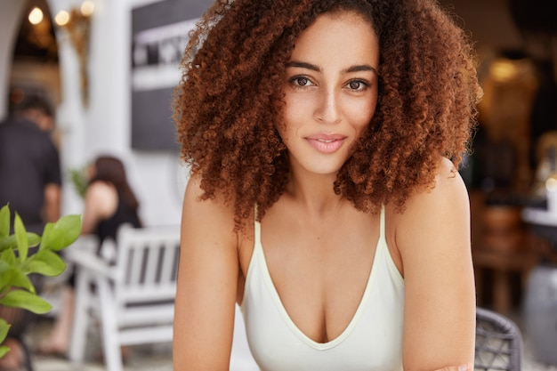 Portrait of beautiful young mixed race african american female model sits against cafe interior, comes for meeting with best friend or has date with boyfriend