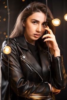 Ritratto di una bellissima giovane modella in giacca di pelle nera in posa vicino alle lampade.