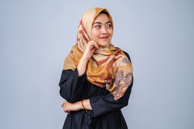 Portrait of beautiful young model in fashionable hijab style posing against grey background