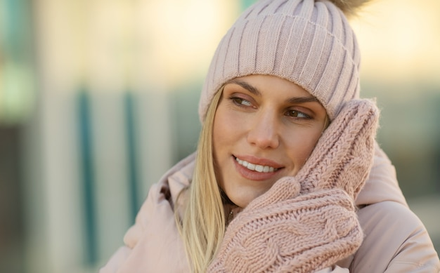 Portrait of a beautiful young model in pink knitted hat and mittens. beautiful natural young smiling blonde woman wearing knitted gloves