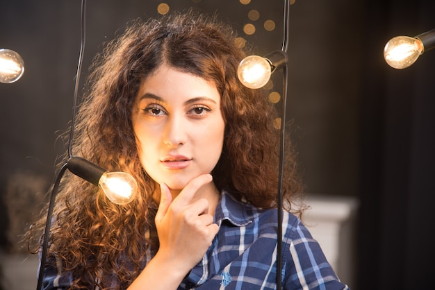 Portrait of a beautiful young model in plaid shirt posing near lamps