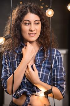 Ritratto di una bellissima giovane modella in camicia a quadri in posa vicino alle lampade