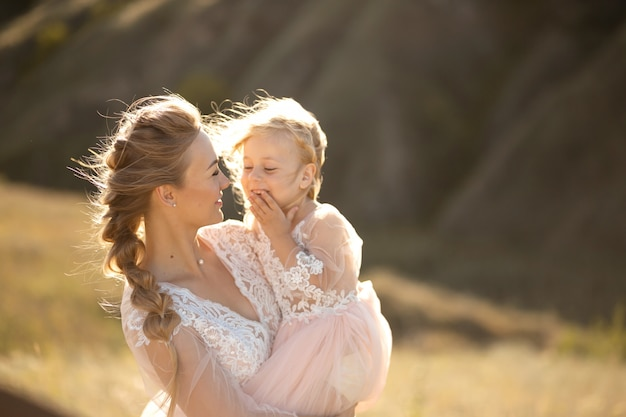 Portrait of a beautiful young mom holds her beloved daughter in her arms. parental love, little princess