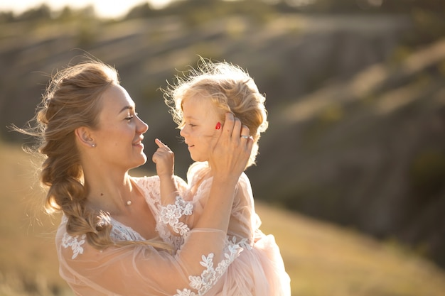 Portrait of a beautiful young mom holds her beloved daughter in her arms