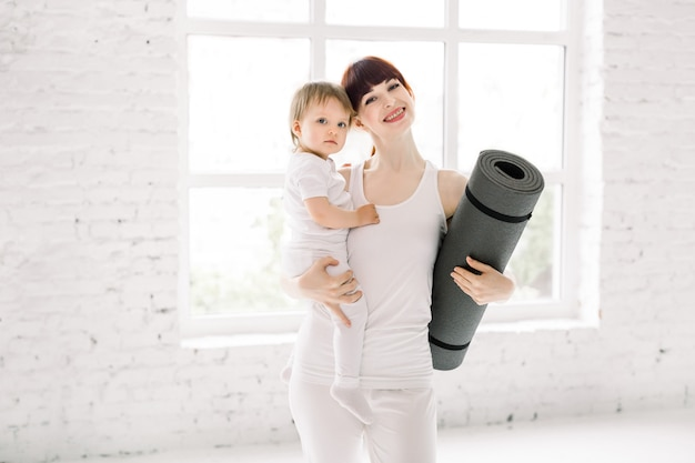 Portrait of beautiful young mom in white sports wear holding her charming little baby girl and yoga mat, looking at camera and smiling