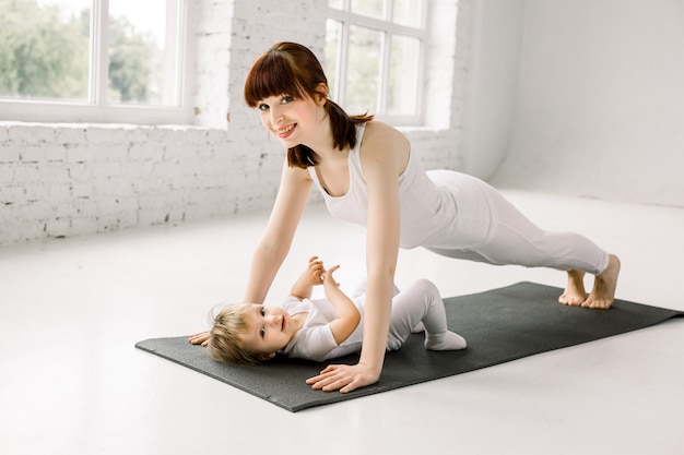 Portrait of beautiful young mother in white sports wear with her charming little baby girl doing exercises on the black mat