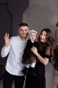 Portrait of beautiful young parents and their cute little daughter hugs and smiling indoors. mother's, father's, baby's day. concept of family. family look