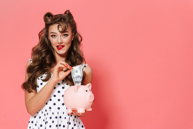Portrait of a beautiful young pin-up girl wearing dress standing isolated, showing piggybank
