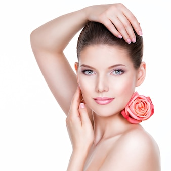 Portrait of beautiful young pretty woman with healthy skin and pink rose near face - isolated on white.