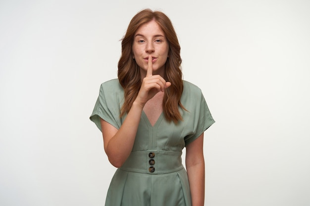 Portrait of beautiful young redhead female in vintage pastel dress posing, raising index finger to lips, asking to keep secret