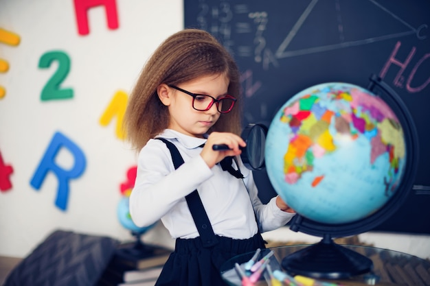 Portrait of a beautiful young schoolgirl girl exploring the globe through a magnifier.