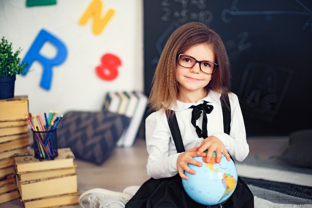 Portrait of a beautiful young schoolgirl girl holding globe sitting on the floor on the rug.