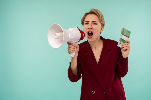 Portrait of beautiful young screaming businesswoman with money and megaphone, on blue background - image