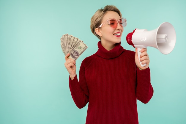 Portrait of beautiful young screaming woman with money and megaphone, on blue background - image