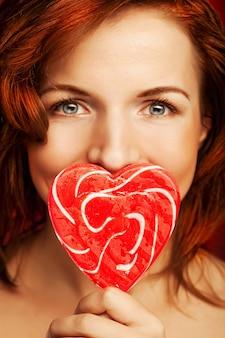 赤いロリポップの心を持つ肖像画の美しい若いセクシーなブロンドの女の子。赤い壁に。