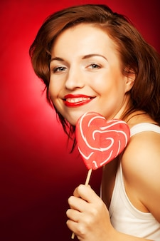 赤いロリポップの心を持つ肖像画の美しい若いセクシーなブロンドの女の子。