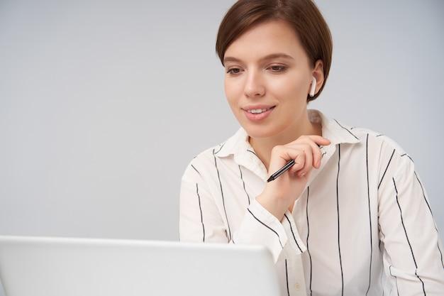 Ritratto di bella giovane signora bruna dai capelli corti con taglio di capelli alla moda alzando la mano con la penna e sorridendo positivamente mentre guarda sullo schermo del suo laptop, posa su bianco