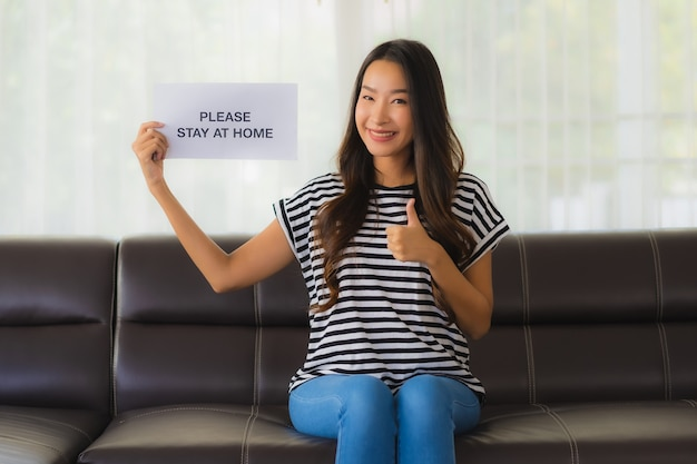 Portrait of beautiful young shows paper with stay home phrase on sofa