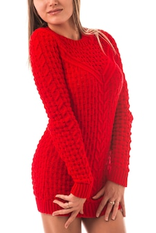 Portrait of a beautiful young slim girl in a red knitted sweater posing. concept of strong warm knitwear.