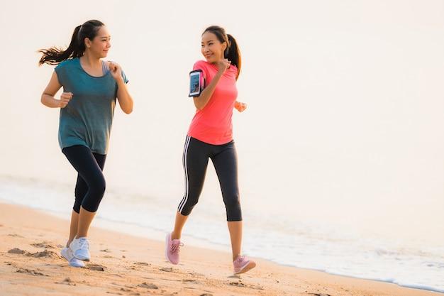 일출 또는 일몰 시간에 바다와 바다 근처 해변에서 세로 아름다운 젊은 스포츠 아시아 여자 실행 및 운동