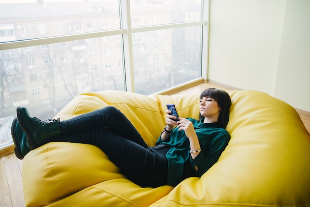 Portrait of a beautiful young stylish business woman lying in a chair bag and use the phone. break in the modern office.