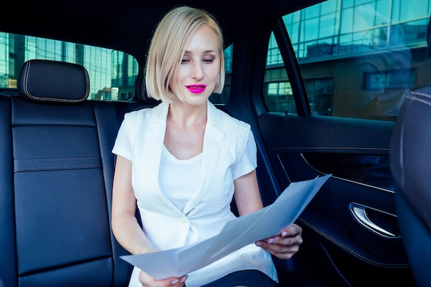 Portrait of beautiful young successful blonde short haircut business woman with makeup bright lipstick in white business suit dress sitting on a leather chair works with securities in car