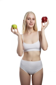 Portrait of beautiful young teen girl holding fresh green and red apple, isolated on white background.