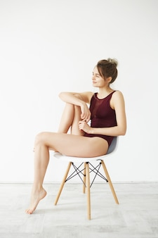 Portrait of beautiful young tender model in burgundy swimwear smiling posing sitting in chair over white wall.