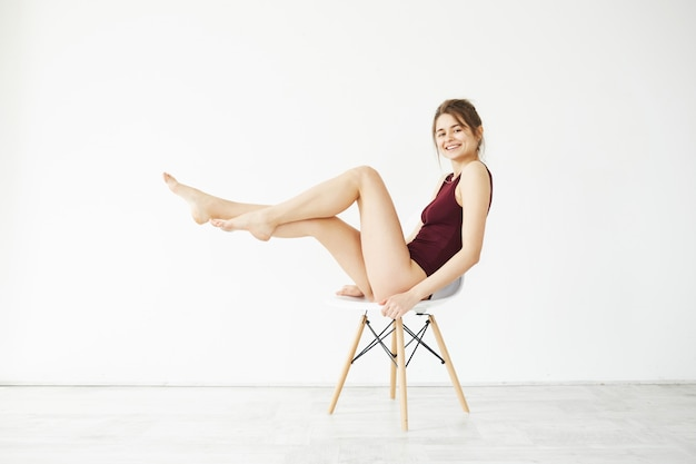 Portrait of beautiful young tender woman in burgundy swimwear smiling posing on chair over white wall.