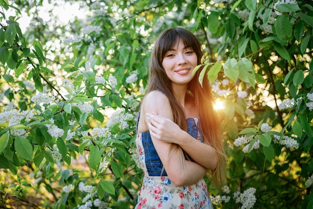 Portrait of a beautiful young woman on the background of a flowering bird cherry bush
