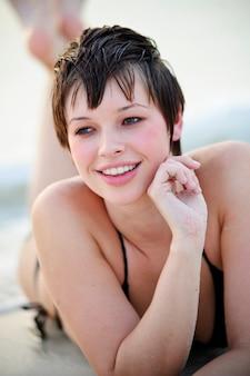 Portrait of beautiful young woman in the beach. female model in bikini having fun outdoors.