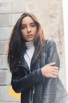Portrait of a beautiful young woman in black leather jacket looking at camera