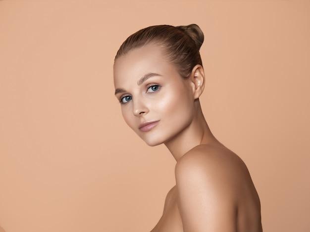 Ritratto di giovane e bella donna in studio marrone