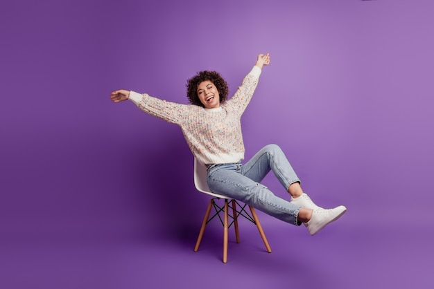 Portrait of beautiful young woman celebrate victory sit chair raise hands rejoice isolated on violet wall