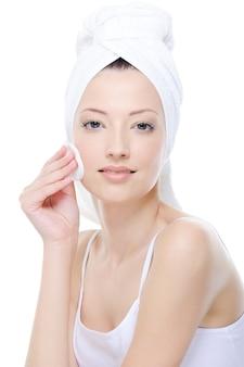 Ritratto di giovane e bella donna che pulisce il viso con un batuffolo di cotone