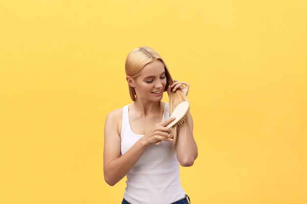 Portrait of beautiful young woman combing her hair, looking at camera and smiling.