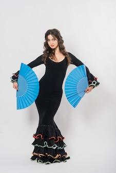 Portrait of beautiful young woman dancing flamenco with fan in studio
