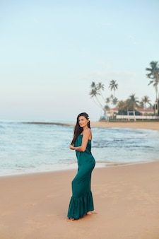 Portrait of beautiful young woman in dress on the beach. pretty girl on tropical beach. freedom concept, holiday, beach, sky background.