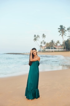 Portrait of beautiful young woman in dress on the beach pretty girl on tropical beach